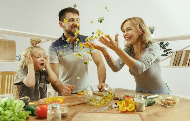 Jolie petite fille et ses beaux parents coupent des légumes dans la cuisine à la maison