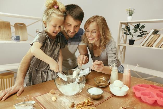 Jolie petite fille et ses beaux parents préparant la pâte pour le gâteau dans la cuisine à la maison