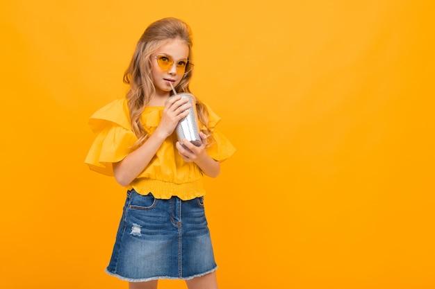 Jolie petite fille avec ses lunettes boit un cocktail et sourit isolé sur fond blanc