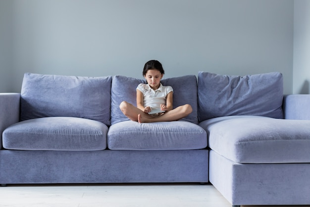 Jolie petite fille avec smartphone sur le sofa