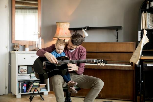 Jolie petite fille et son beau père jouent de la guitare
