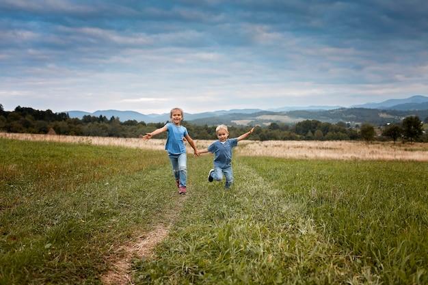 Jolie petite fille avec son jeune frère courant ensemble main dans la main à travers une belle prairie dans les montagnes, vacances de printemps en famille. amusement en plein air et activité saine, mode de vie des gens