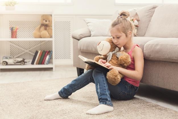 Jolie petite fille et son livre de lecture d'ours en peluche. jolie enfant à la maison, assise sur le sol près du canapé avec son jouet préféré, concept d'éducation et de développement précoce, espace de copie