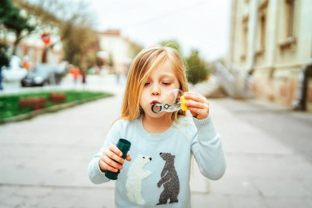 Jolie petite fille soufflant des bulles en plein air
