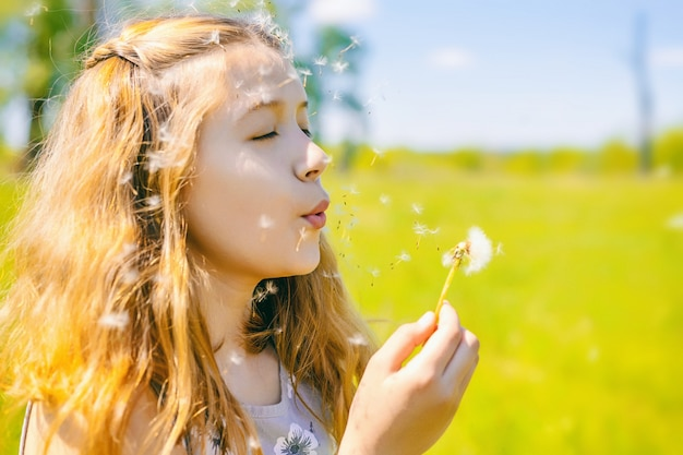 Jolie petite fille souffle les pissenlits par une journée ensoleillée à l'extérieur
