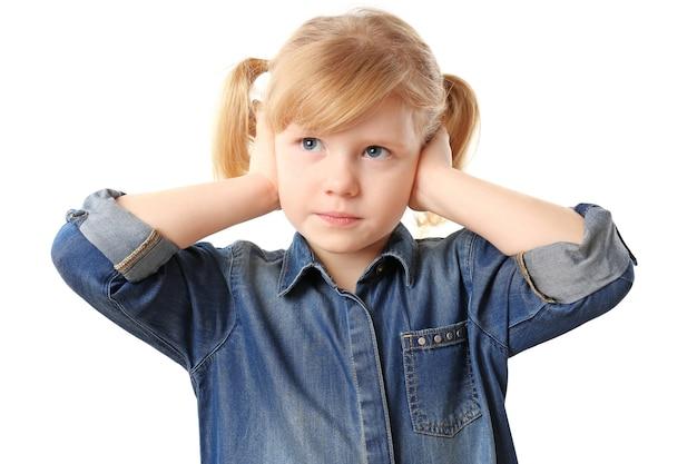 Jolie petite fille souffrant de maux d'oreille, sur blanc