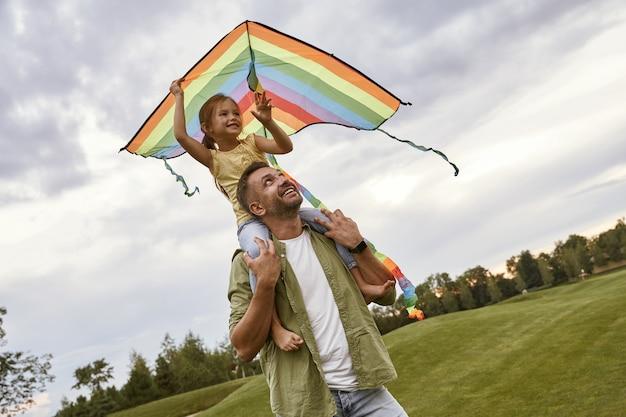 Jolie petite fille souriante assise sur les épaules de son père et jouant avec un petit cerf-volant coloré