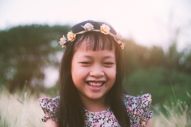 Jolie petite fille souriante avec une couronne de fleurs dans un champ de prairie