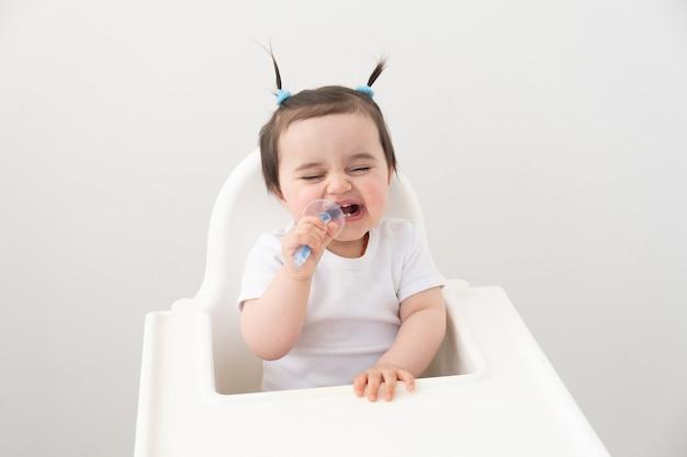 Jolie petite fille souriante et se brosser les dents avec une brosse de couleur