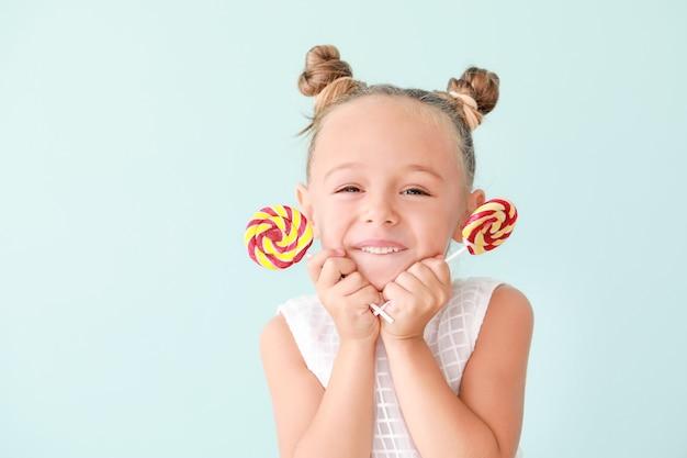 Jolie petite fille avec des sucettes sucrées sur la couleur