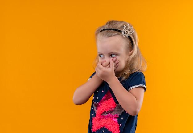 Une jolie petite fille surprenante portant une chemise bleu marine en bandeau couronne tenant la main sur la bouche et à côté sur un mur orange