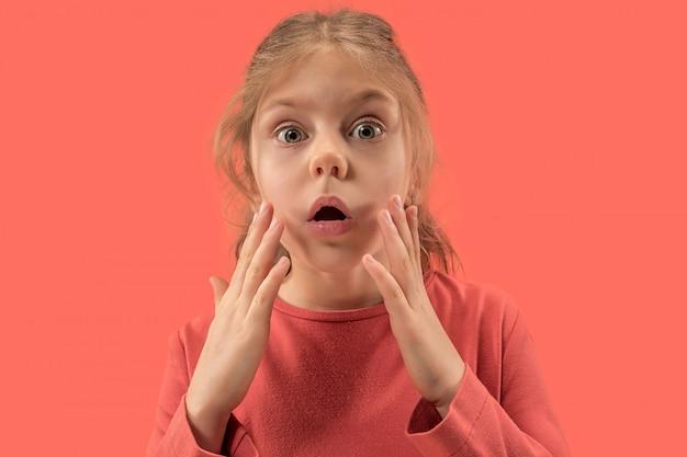 Jolie petite fille surprise en robe corail aux cheveux longs souriant
