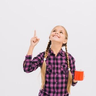 Jolie petite fille avec une tasse pointant vers le haut