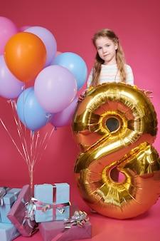 Jolie petite fille tenant un ballon d'or sous forme de numéro huit tout en posant à la fête d'anniversaire sur le mur rose