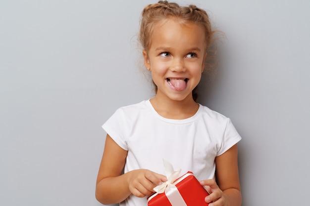 Jolie petite fille tenant un coffret rouge dans ses mains