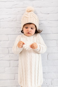 Jolie petite fille tenant un flocon de neige