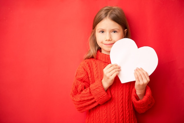Jolie petite fille tenant un grand coeur de papier, sur fond rouge