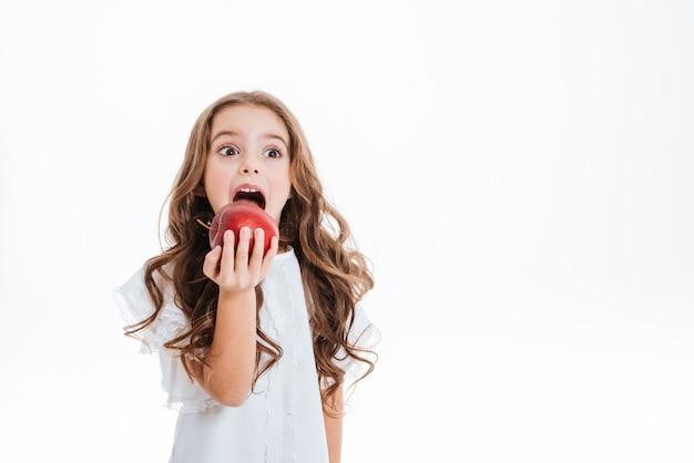 Jolie petite fille tenant et mange une pomme rouge