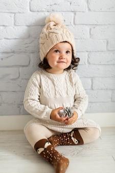 Jolie petite fille tenant une pomme de pin