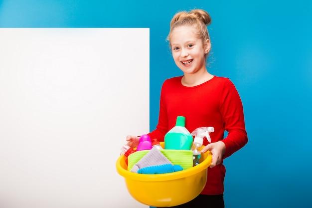 Une jolie petite fille tenant des produits de nettoyage faisant le ménage