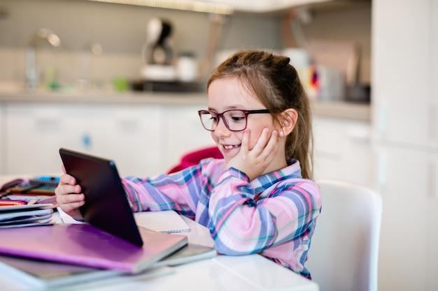 Jolie petite fille tenant une tablette tout en faisant ses devoirs. éducation en ligne.