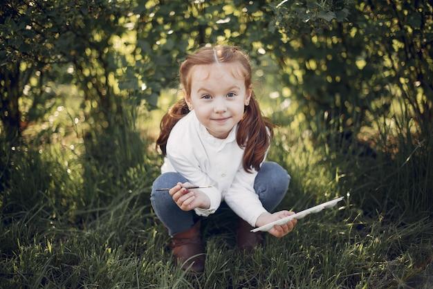 Jolie petite fille en train de peindre dans un parc