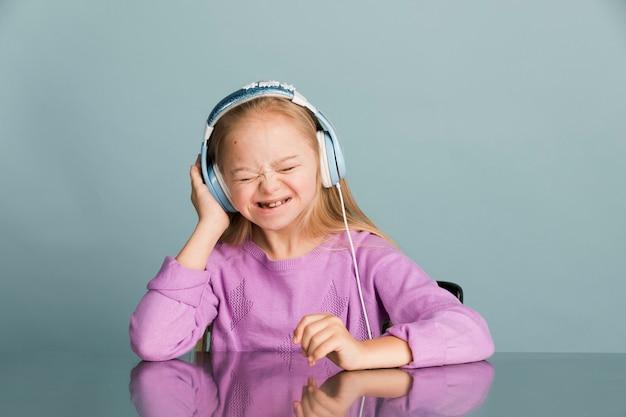 Jolie petite fille trisomique écoutant de la musique