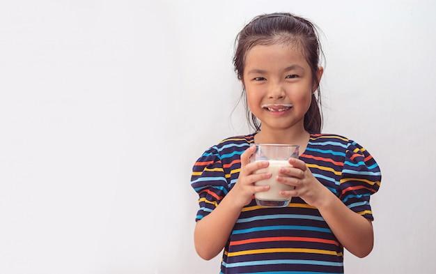Jolie petite fille avec un verre de lait