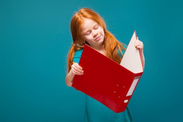 Jolie petite fille en vêtements bleus avec de longs cheveux roux prend soin des papiers
