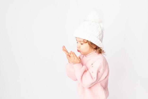 Jolie petite fille en vêtements d'hiver rose sur fond blanc souffle ses mains, espace pour le texte