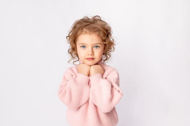 Jolie petite fille en vêtements d'hiver roses sur fond blanc, espace pour le texte