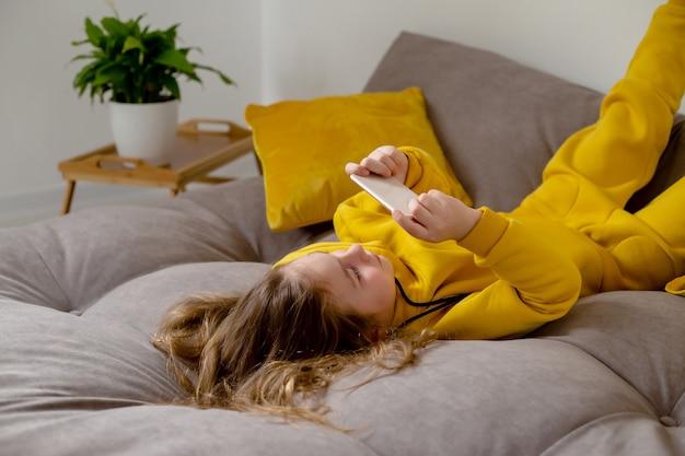 Jolie petite fille en vêtements jaunes est allongée sur le dos sur le lit et tient un smartphone dans ses mains