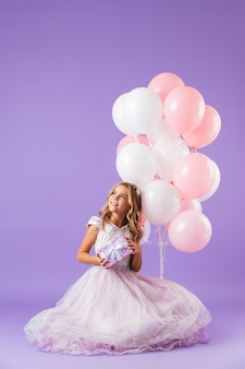 Jolie petite fille vêtue d'une robe de princesse assise isolée sur un mur violet, tenant un bouquet de ballons et une boîte-cadeau