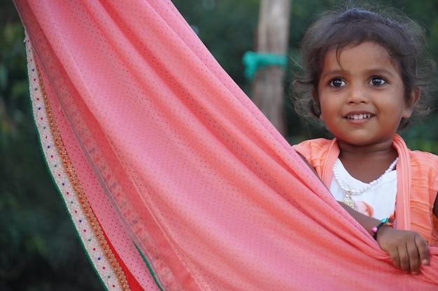 Une jolie petite fille avec la zone d'un sari, portée sur une épaule ou sur la tête
