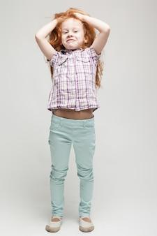 Jolie petite rousse en chemise à carreaux, pantalon bleu vif et bottes blanches