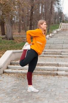 Une jolie photo d'une femme faisant l'étirement avant de courir dans le parc