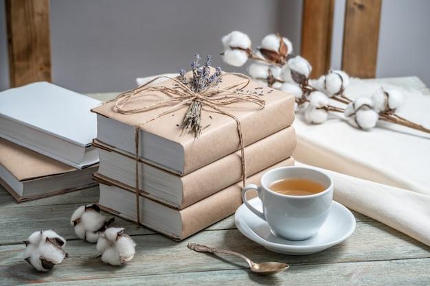 Jolie pile de livres avec des couvertures en papier craft enveloppées dans une corde et décorées de lavande