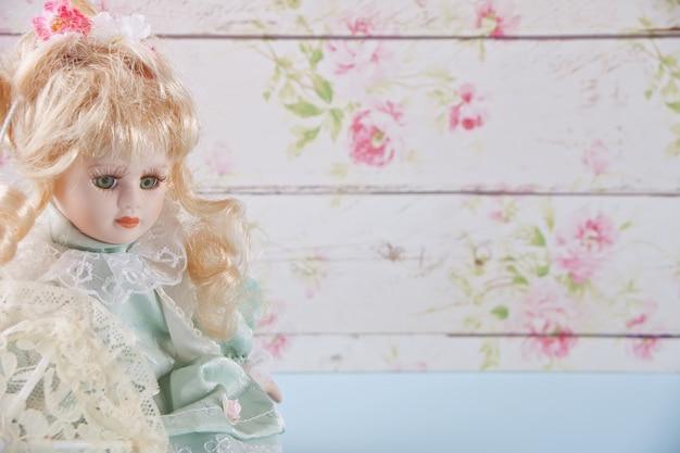 Jolie poupée vintage sur le mur de fleurs sur le fond
