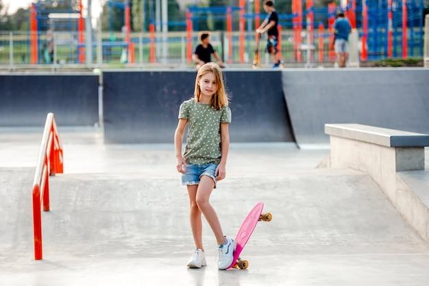 Jolie préadolescente avec planche à roulettes à l'extérieur. enfant de patineuse près de la rampe d'équitation du parc