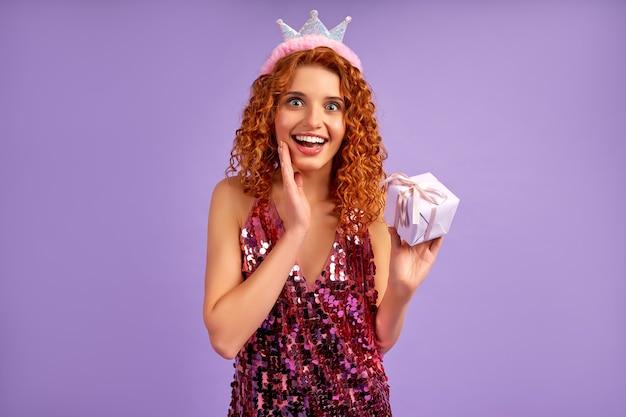 Jolie princesse aux cheveux roux avec des boucles dans une robe brillante et une couronne sur la tête tenant un cadeau isolé sur violet