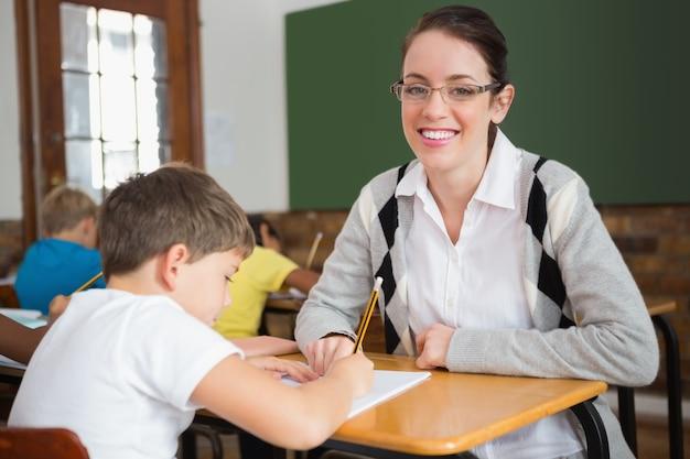 Jolie professeur aidant élève en salle de classe, souriant à la caméra