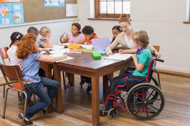 Jolie professeur aidant les élèves en salle de classe