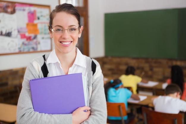 Jolie professeur souriant à la caméra à l'arrière de la salle de classe