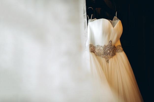 Jolie robe de mariée blanche accrochée dans la chambre de la mariée