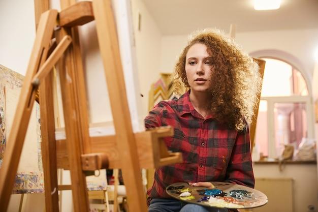Jolie rousse bouclée centrée sur l'artiste dessine un tableau