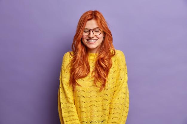 Jolie rousse femme de race blanche ferme les yeux et sourit largement rit de quelque chose de drôle habillé en pull jaune tricoté.