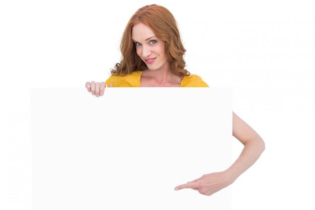 Jolie rousse montrant une affiche
