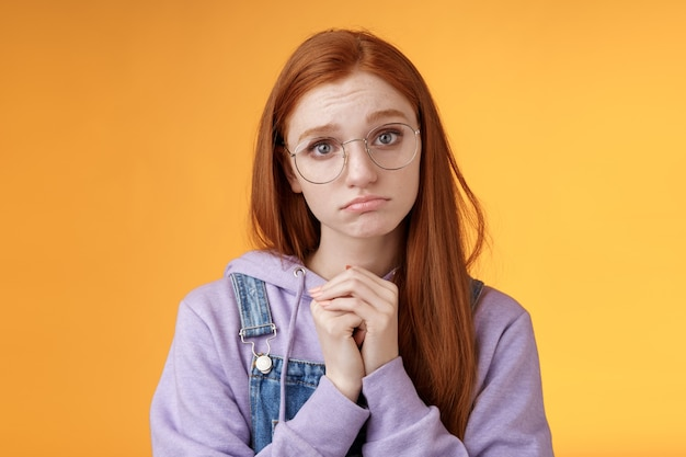 Jolie s'il-vous-plaît. clingy jeune triste bouder fille rousse portant des lunettes faisant la moue idiot appuyez sur les paumes mendicité geste suppliant de recevoir de l'aide promet d'être bon demander faveur, fond orange