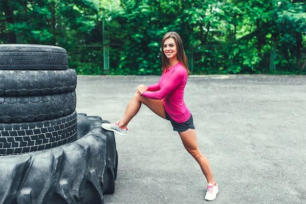 Jolie séance d'entraînement sportive en plein air avec gros pneu