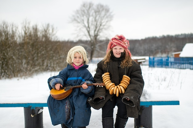 Jolie soeurs du village caucasien s'asseoir sur le banc avec balalaïka